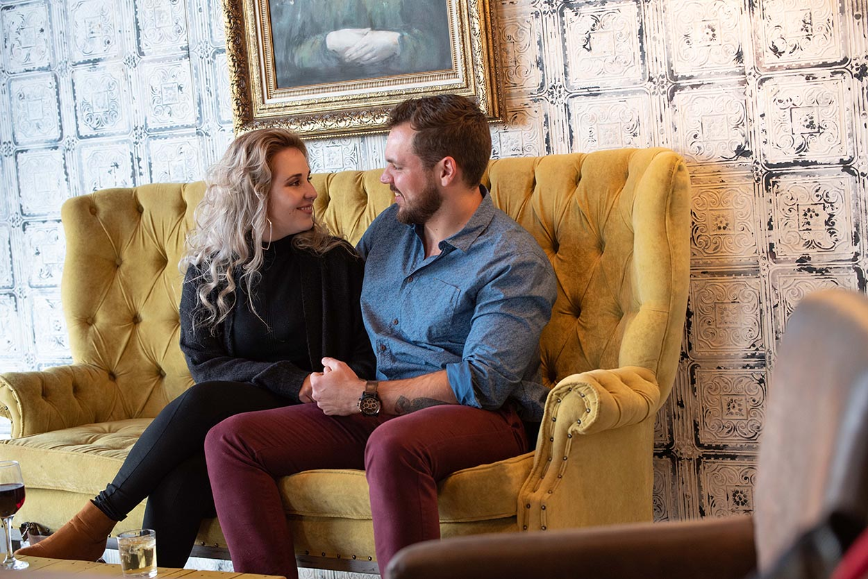 couple in coffee shop for couple photos with Mudboots in Bloemfontein on yellow chair