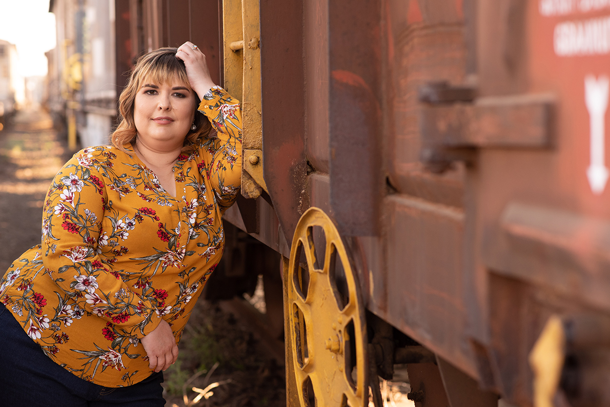 portrait photos bloemfontein by Mudboots women in Mustard shirt portrait photography next to train
