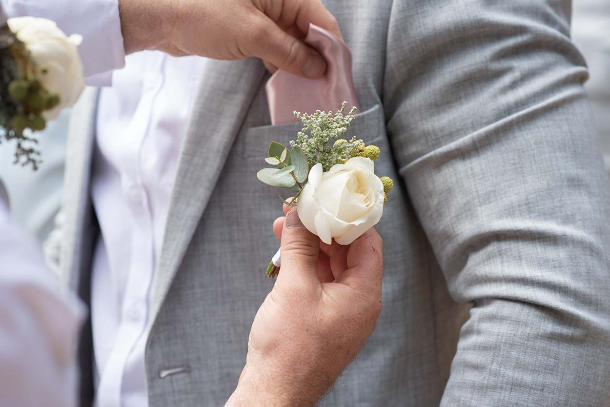 groom in grey suit putting on white rose by mudboots photography and film