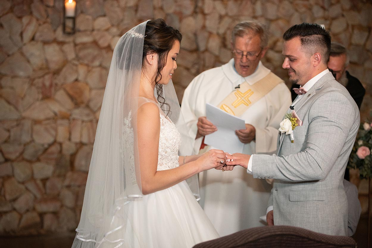 bride and groom exchanging rings by mudboots photography tres jolie